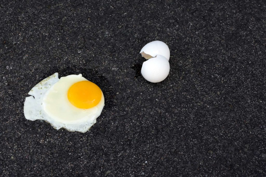 Fried egg and a cracked eggshell on the sidewalk