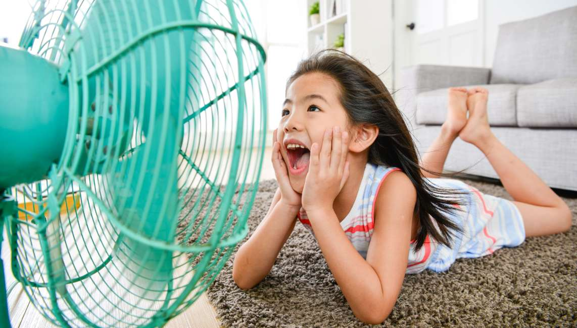 A girl sits in front of a fan to cool down